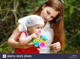 cute toddler baby sitting on mom hands playing with toy