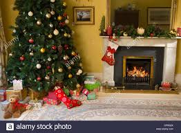 christmas tree and gifts by fireplace stock photo royalty free