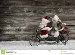 funny wooden christmas background with two santa claus on a bicy