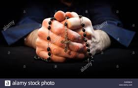 holding rosary and cross while praying stock photo