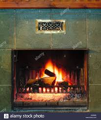 fire and burning firewood in old fireplace concept of coziness