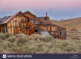 old wooden houses at dawn with sierra nevada snow tipped mountain