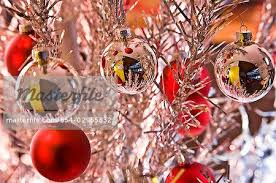 silver and red christmas tree bulb ornaments hanging from bright