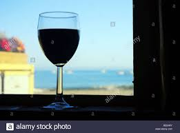 wine glass silhouette silhouette of a glass of red wine in a window sill with the ocean