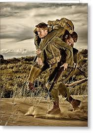 two wwii soldiers fireman s carry of wounded soldier photograph