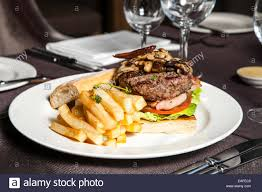 Elegant Table Settings by Gourmet Burger With Fries With Elegant Table Settings Stock Photo
