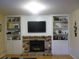 living room high white wooden bookcase with brick stone fireplace