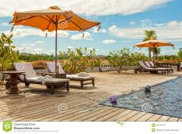 Poolside Table And Chairs Beach Lounge Chairs With Towels Under Umbrella At The Poolside O