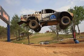 monster trucks racing in mud traxxas and torc land in michigan to invade red bud traxxas