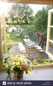 Setting A Table by Man Setting A Table In A Garden Klein Thurow Roggendorf Stock