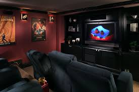 home theater walls black tv on black wooden cabinet with dark blue sofa on grey rug