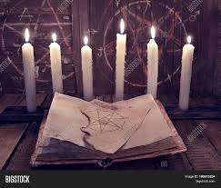 candles for halloween magic book with pentagram and evil candles for occult ritual