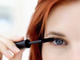 red haired woman applying mascara