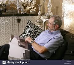 senior man reading sofa luxury living room black and silver stock