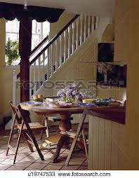 stock photo of circular dining table and wooden chairs in small