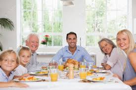 family smiling around the dinner table at thanksgiving stock photo