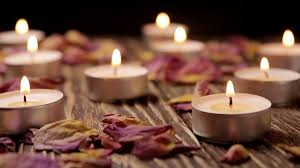 lighted small candles and dried flowers roses on a wooden table