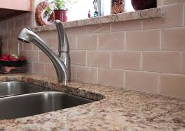 peach subway tile backsplash with light cream granite countertops