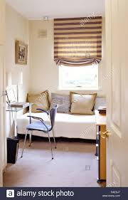 striped roman blind on window above sofa in modern home office
