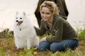 american eskimo dog vector a young woman siting in grass petting her american eskimo dog