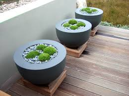 contemporary planters with moss and gravel raised pads on decking