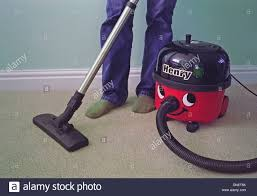 caucasian man vacuuming a carpet with a henry vacuum cleaner model