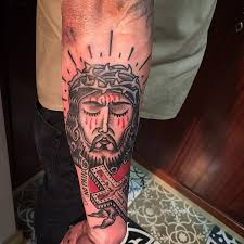 eyed jesus with a cross on forearm