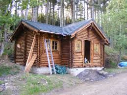 small design log cabin pole barn that has single white door and