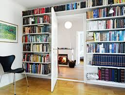 gorgeous bookshelf wall with simple door and black chair on wood