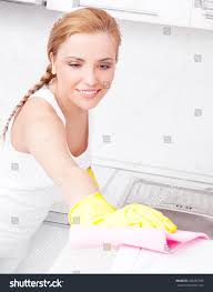 Furniture In The Kitchen by Beautiful Young Housewife Wearing Gloves Cleaning Stock Photo