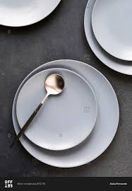 simple modern white dishes and spoon on surface stock photo