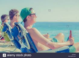 Chairs On A Beach Young Men Drinking Beer In Deck Chairs On Sunny Beach Stock Photo