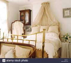 coronet with cream voile drapes above brass bed with cream