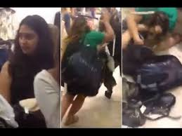 women fighting over clothes on floor of shop as stunned customers