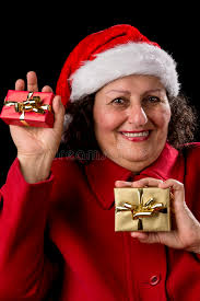 what to get an elderly woman for christmas happy woman with santa hat and two gifts stock photo