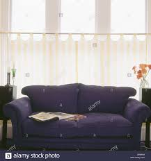 dark blue sofa in front of yellow and white striped cafe curtains