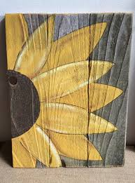 this is a painted sunflower painted on reclaimed fence