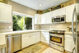 white kitchen cabinets with steel appliances and light tone