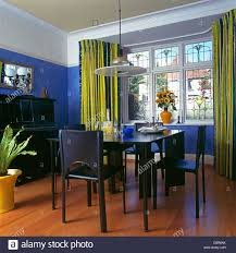 disc light above black chairs and table in modern blue dining room