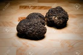 italian truffles a pair of black italian truffles leaning on a wooden cutting