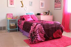pink floral bedding set on the bed and pink fur rug connected by