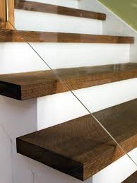 Glass Stair Rail by Reclaimed Wood Planks In A Dark Stain Are Used For The Stair