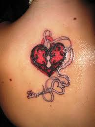 pink and black heart shape lock and key tattoo on upper back by