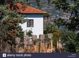 old stone house painted white with red tile roof behind castle