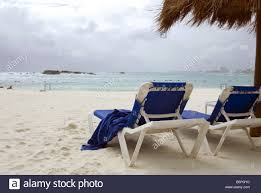 Beach Lounge Chairs Beach Lounge Chairs Sit Empty On Shore Of Caribbean Ocean In