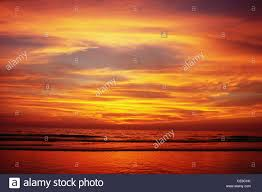 shades of yellow orange red warm clouds sky and sea after sunset