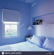 blue blind on window in modern blue apartment bedroom with alcove