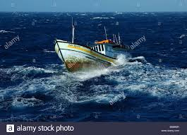 fishing boat in rough sea stock photo royalty free image