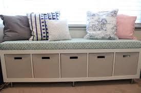 long white window storage bench with drawers and patterned cushion