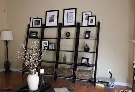 four black leaning wall shelves with baskets and framed artworks